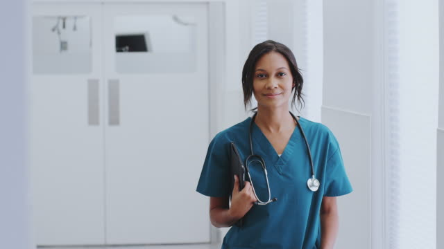 Portrait Of Female Doctor With Stethoscope Wearing Scrubs In Hospital Corridor With Digital Tablet