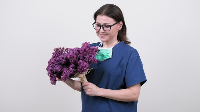 Portrait of female doctor with stethoscope with bouquet of lilac flowers. Portrait of female doctor with stethoscope with bouquet of lilac flowers. World health day, happy nurse with flowers on white background. High quality 4k footage world health day stock videos & royalty-free footage