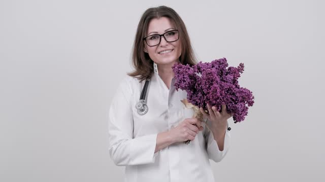 Portrait of female doctor with stethoscope with bouquet of lilac flowers. World health day, happy nurse with flowers on white background. High quality 4k footage Portrait of female doctor with stethoscope with bouquet of lilac flowers. World health day, happy nurse with flowers on white background. High quality 4k footage world health day stock videos & royalty-free footage