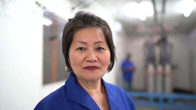 vídeos de stock e filmes b-roll de portrait of female employee looking at camera in industry - 55 59 anos
