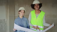 istock Portrait of female engineer holding blueprint at construction site 1180187585