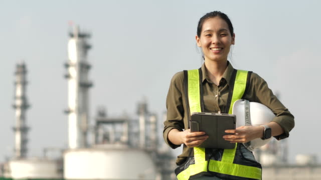 Portrait of Female engineer smiling to Camera at industrial plant Portrait of Female engineer smiling to Camera at industrial plant work helmet stock videos & royalty-free footage