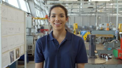 atölye kameraya doğru yürüyen kadın mühendis portresi - dişiler stok videoları ve detay görüntü çekimi
