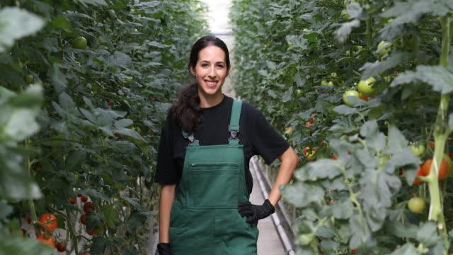 portrait of female farmer standing in greenhouse - bio food video stock e b–roll