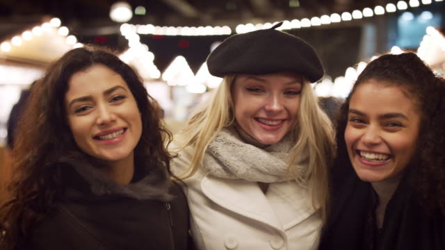Portrait Of Female Friends Enjoying Christmas Market At Night video