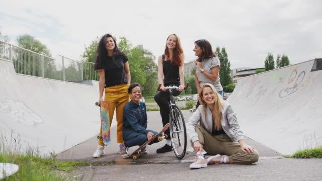 porträt von weiblichen freunden mit skateboards und bike standing in urban skate park - freundin stock-videos und b-roll-filmmaterial