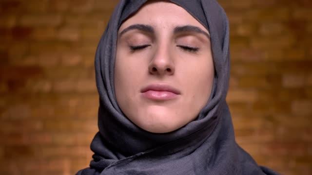 porträtt av kvinnliga händer gör smink med hjälp av platt borste för medelålders muslimsk kvinna i hijab på bricken vägg bakgrund. - hijab bildbanksvideor och videomaterial från bakom kulisserna