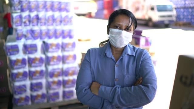 portrait of female logistics employee at delivery company - with face mask - prodotti supermercato video stock e b–roll
