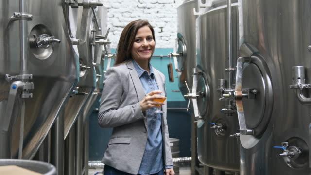 porträtt av kvinnlig chef bryggeri provsmakning ölprov - dom bildbanksvideor och videomaterial från bakom kulisserna