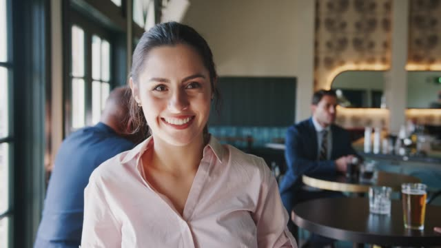 portret kobiety kierownik ruchliwego cocktail baru w restauracji z klientami uśmiecha się do kamery - kelner filmów i materiałów b-roll