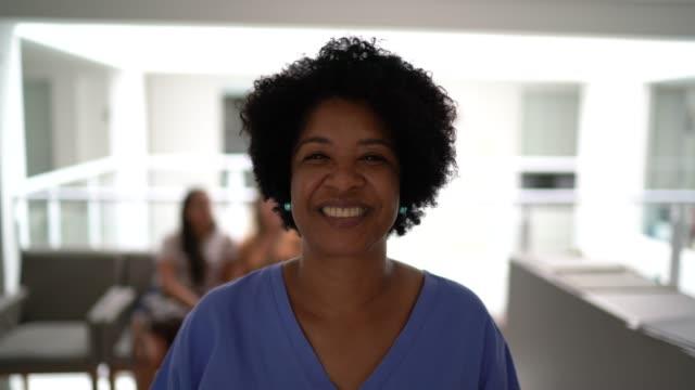 vídeos y material grabado en eventos de stock de retrato de enfermera madura en el hospital - sonrisa con dientes
