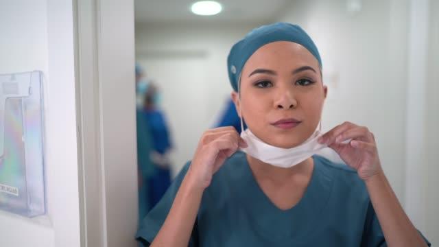 Portrait of female nurse dressing up face mask at hospital video