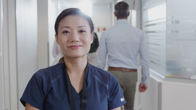 Portrait Of Female Nurse Wearing Scrubs With Digital Tablet In Busy Hospital Corridor video