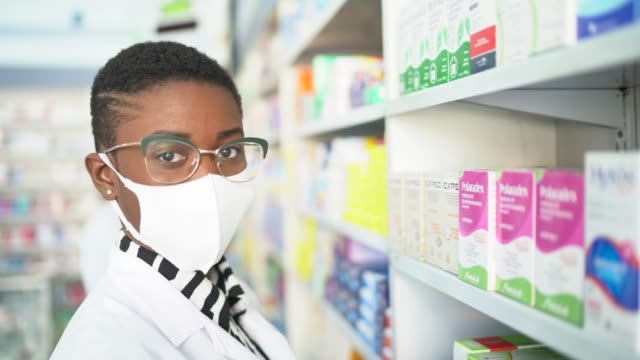 Portrait of female pharmacist picking some drugs with face mask at pharmacy