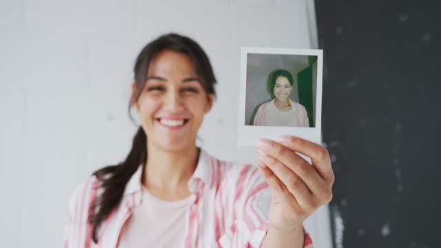 stockvideo's en b-roll-footage met portret van vrouwelijke fotograaf op foto shoot houden van instant polaroid print in studioê - polaroid