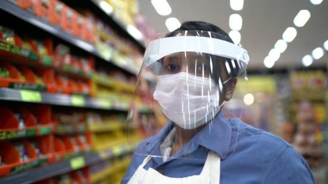 vídeos de stock e filmes b-roll de portrait of female senior supermarket employee or owner with face shield using digital tablet - supermarket worker