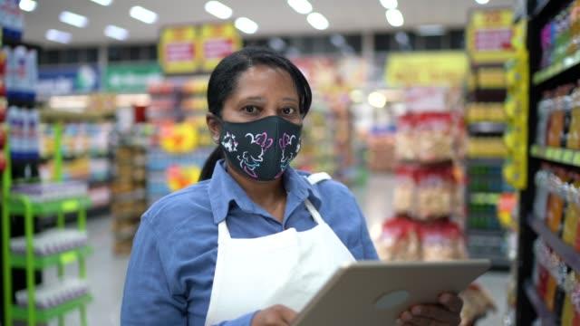 porträt einer weiblichen senior-supermarkt-mitarbeiterin oder -besitzerin mit gesichtsmaske mit digitalem tablet - krankheitsverhinderung stock-videos und b-roll-filmmaterial