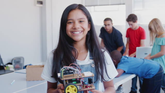 Portrait Of Female Student Holding Robot Vehicle In After School Computer Coding Class video