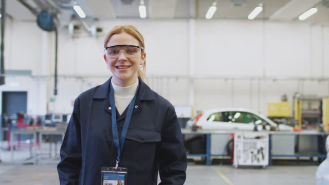 portrait of female student wearing safety glasses studying for auto mechanic apprenticeship - apprendista video stock e b–roll