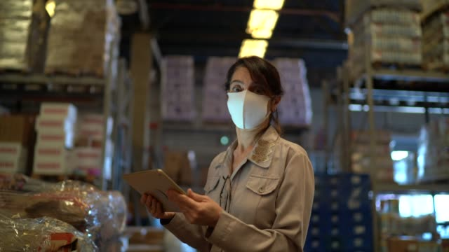 portrait of female warehouse worker with face mask using digital tablet - prodotti supermercato video stock e b–roll
