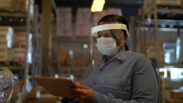 portrait of female warehouse worker with face shield using digital tablet - prodotti supermercato video stock e b–roll