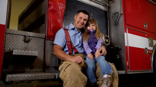 Portrait of firefighter and young girl video