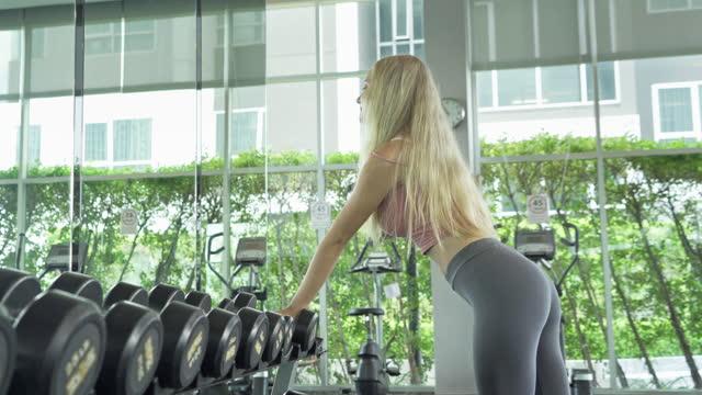 ritratto di donna bianca in forma sana, persona caucasica, fare esercizio fisico, allenarsi e allenarsi in palestra o centro fitness nel concetto di sport e ricreazione. attività di stile di vita. - dorso umano video stock e b–roll
