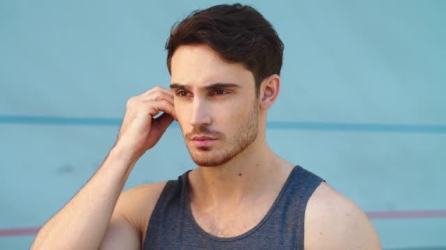 portrait of fitness man wearing earphones on modern track - auricolari wireless video stock e b–roll