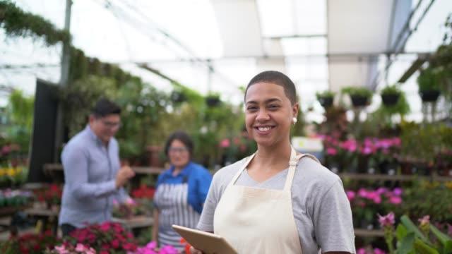 porträtt av florist använda tablet på small business blomsteraffär - frilansarbete bildbanksvideor och videomaterial från bakom kulisserna