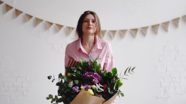 Portrait of florist with big modern bouquet of different flowers Portrait of florist with big modern bouquet of different flowers. 4k bunch stock videos & royalty-free footage