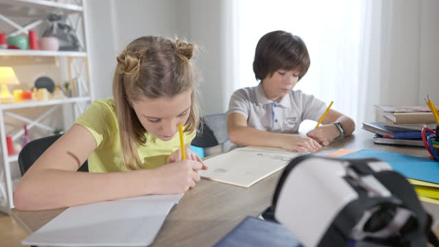 Portrait of focused genius girl thinking and writing in workbook with blurred boy drawing at background. Concentrated intelligent Caucasian children studying in modern classroom at desk. Education.