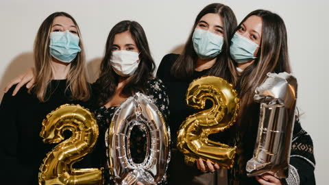 Portrait of four friends celebrating 2021 New Year's Eve together - Stop motion video Portrait of four friends celebrating 2021 New Year's Eve together - Stop motion video. They are looking at camera and smiling. They are wearing protective face masks. happy new year stock videos & royalty-free footage