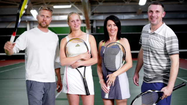 Portrait of four happy friends dressed in sport outfit standing with rackets in recreation area looking at camera. Two couples spending leisure time together playing tennis at indoor court video