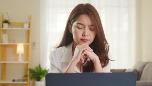 フリーランスのアジアの女性の肖像画は、自宅のリビングルームでラップトップのハードワークを使用してカジュアルに着用します。 - 悩む点の映像素材/bロール