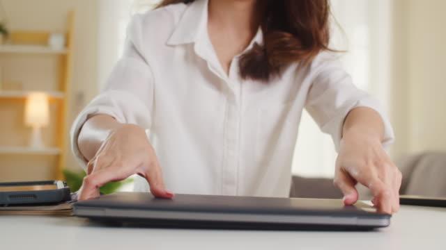 porträt freiberuflicher asia-frauen, die lässig mit einem laptop arbeiten, der zu hause im wohnzimmer arbeitet. - freischaffender stock-videos und b-roll-filmmaterial