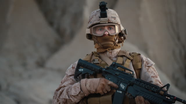 vídeos de stock e filmes b-roll de portrait of fully equipped and armed soldier wearing safety glasses in desert environment - fuzileiro naval