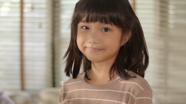 porträtt av funny cute asiatiska little girl tittar på kameran poserar och ler med roliga, positiva, och glada känslor medan du står i vardagsrummet hemma. - flickbaby bildbanksvideor och videomaterial från bakom kulisserna