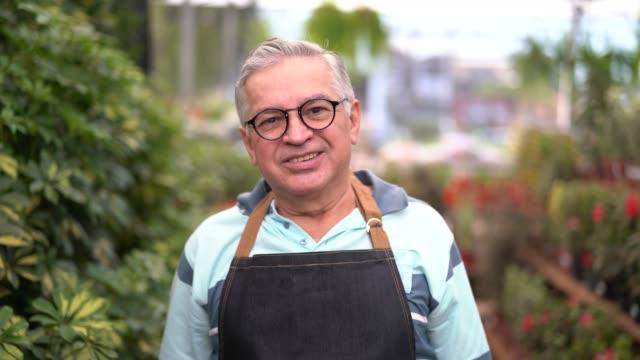 ritratto di dipendente / proprietario del mercato del giardino - 60 69 anni video stock e b–roll