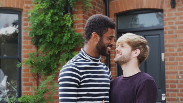 Portrait Of Gay Male Couple Standing Outside New Home On Moving Day Together Kissing video