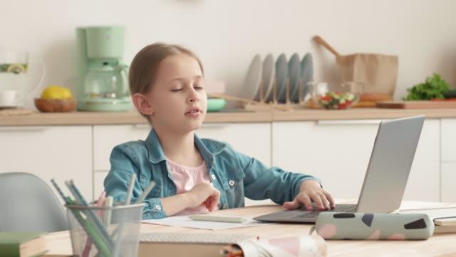 портрет девушки, делая домашнее задание на кухне - covid testing стоковые видео и кадры b-roll