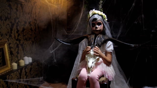 Portrait of girl dressed in Halloween Santa muerte costume  holding a goat scull in of old dark Gothic interior covered with cobwebs and mysterious fog and  changing lighting. 4K slow motion 50 fps