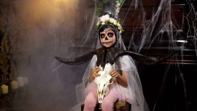 Portrait of girl dressed in Halloween Santa muerte costume  holding a goat scull against background of old dark Gothic interior covered with cobwebs and mysterious fog. 4K slow motion 50 fps