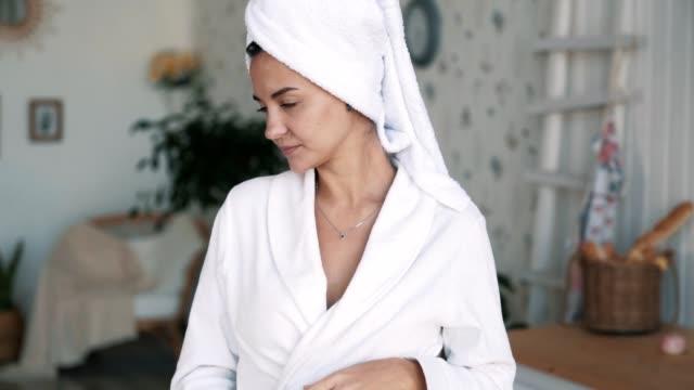 vidéos et rushes de verticale de fille dans le peignoir, avec la serviette sur le café ou le thé de boissons de tête, mouvement lent - peignoir