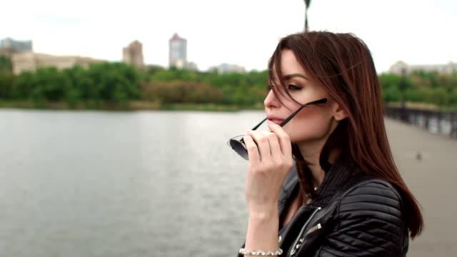 Portrait de jeune fille à lunettes de soleil sur le pont de la rivière. - Vidéo