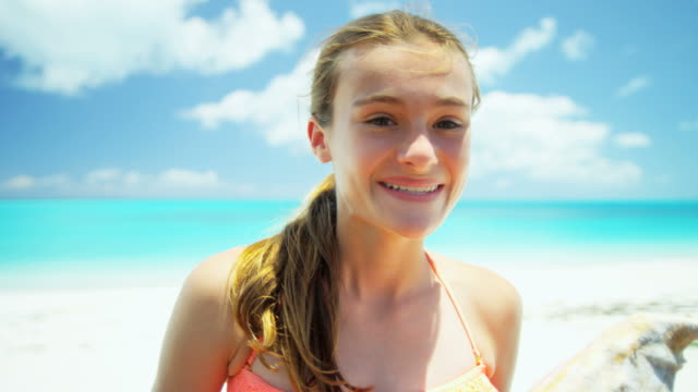 vídeos de stock e filmes b-roll de portrait of girl on beach holding conch shell - bugio