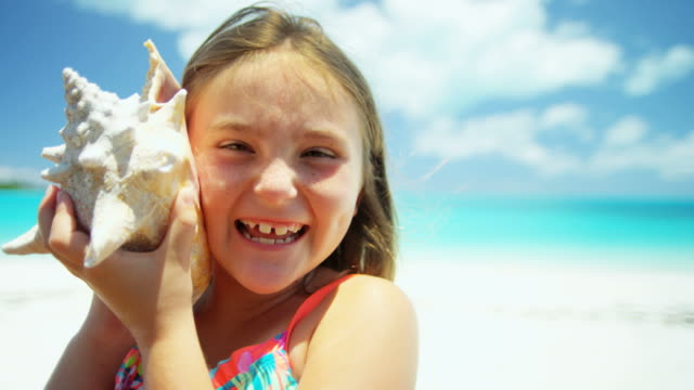 Portrait of girl on beach holding conch shell portrait young female Caucasian American cute girl outdoor lifestyle travel Caribbean beach destination vacation tourism conch shell RED DRAGON animal shell stock videos & royalty-free footage