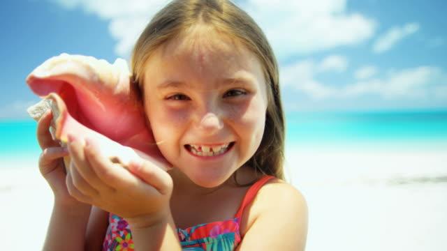 vidéos et rushes de portrait de jeune fille sur la plage avec la coquille de conque - coquillage