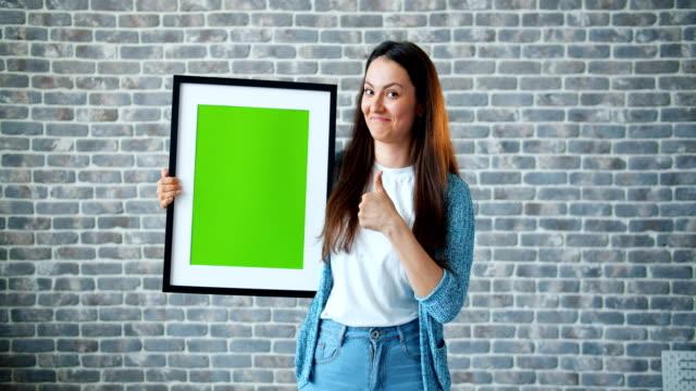 porträtt av flicka som pekar på grön skärmbild som visar tummen upp leende - fotoram bildbanksvideor och videomaterial från bakom kulisserna