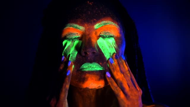 Portrait of girl smears and rubs fluorescent paint under eyes. Dye glowing near UV black light. Woman with braids in neon light. Night club, party, halloween psychedelic concepts