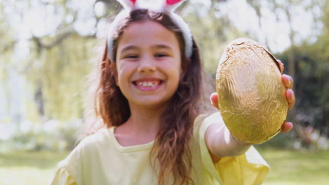 Portrait of girl wearing bunny ears on Easter egg hunt outdoors at home holding up chocolate egg to camera and smiling - shot in slow motion